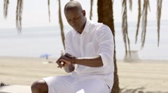 Seated black male model checking his watch - stock footage