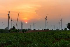 Wind turbine power generator at twilight - stock photo