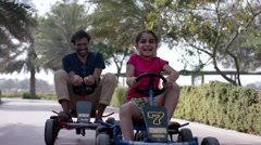 Father and daughter driving pedal go kart at park. Stock Footage