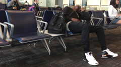 Young man sleeping in airport terminal Stock Footage