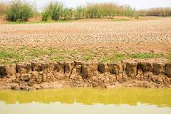 cracked soil in the bottom of a river showing drought - stock photo