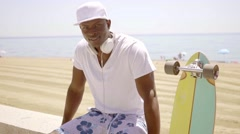 Black skater next to his board and sandy beach Stock Footage