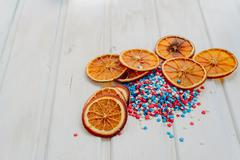Slices of dried oranges and star sprinkles on a white background with copyspa Stock Photos