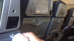 Plugging in on airplane - smart device into back of chair Stock Footage