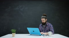 4K Hipster man working on laptop & looking at chalkboard behind for inspiration - stock footage