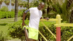 Bald black man in bright green shorts and ear buds Stock Footage