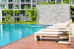 Chaise longue and swimming pool Stock Photos