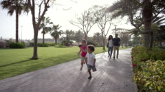 Parents with children running at park. Stock Footage