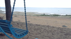 Swinging blue swing with not a single person on a deserted beach. Stock Footage