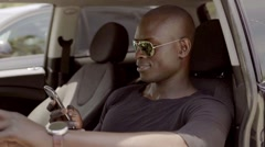 African man driving a car and checking his mobile - stock footage