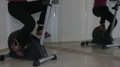 Women's legs in sport shoes pedaling on a stationary bike in the gym - stock footage