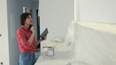 Young woman using tablet computer during renovation at her new home Stock Footage