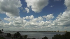 Taymlaps fast flying clouds over the river from the bridge view Stock Footage