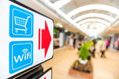 The red arrows on the signs, there is wifi and shopping. - stock photo