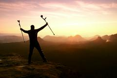 Happy man with broken leg and medicine crutch.  Hiker with leg in immobilizer - stock photo