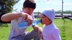 The father of the child gives to drink water - stock footage
