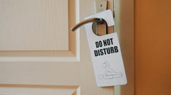 Door hanger do not disturb on handle of a hotel room - stock footage