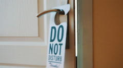 Swinging Do No Disturb sign at hotel room door - stock footage