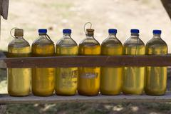 Gasoline for motorbikes sold from whisky bottles by a roadside vendor Stock Photos