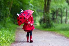 Little girl walking in the rain Stock Photos