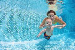 Baby with mother learn to swim underwater in swimming pool Stock Photos