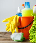 Bucket with cleaning items on light background - stock photo
