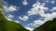 Gentle white clouds quickly run over green valley, mountain landscape scene Stock Footage