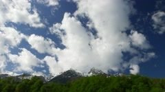 Cumulus clouds whirl above snowy peaks, timelapse shot Stock Footage