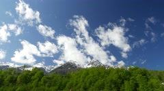 White clouds wreathe over rocky mountains peaks, timelapse at sunny day Stock Footage