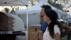 Chef taking order from couple at food stall. Stock Footage