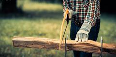 Senior man sawing a log handsaw closeup Stock Photos