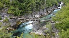 Old bridge across mountain river Stock Footage