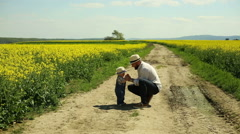 Father playing with baby on a dirt road at the village Stock Footage