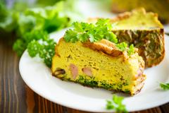 baked omelette with sausages and greens - stock photo