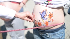 Measuring pregnant female abdomen with body art picture - stock footage