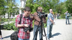 Two Videographers with a Camcorders at the Scene removes a Report at the Park Stock Footage