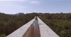 Tourist girl walk thru the ancient devil's aqueduct Stock Footage