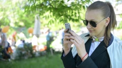Beautiful young girl woman doing photos on mobile phone in park Stock Footage
