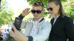 Beautiful young friends boy and girl doing selfie photos on mobile phone in park Stock Footage