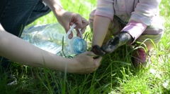 Mom washes with water dirty hands painted black of baby girl in park sunny day - stock footage