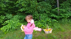 Girl child eats banana in a summer forest. - stock footage
