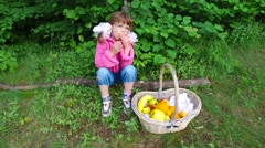 Girl child eats apricots in summer forest. - stock footage