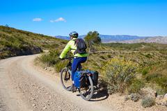 Biker MTB cycle tourism with panniers in Spain - stock photo