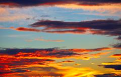 Sunset orange clouds in a blue sky - stock photo