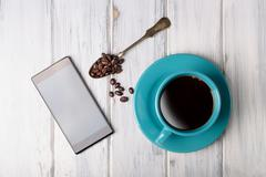 Coffee and smart phone on the table - stock photo