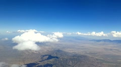 Airline passenger POV high above the clouds and desert Stock Footage