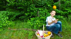 Boy teenager throws an orange. Boy trying to juggle. Evening summer forest. Stock Footage