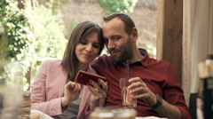 Young couple using smartphone while sitting in cafe in garden Stock Footage