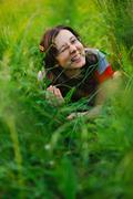 Happy woman lying in green grass Stock Photos