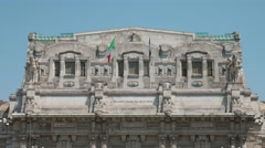 Italian and European flags fluttering in the wind on Milan Central Station - stock footage